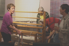 Judy Hasinoff explains  the weaving process to Wendy Aitkens while setting up the loom on display  for Woven In Time. Photo by Richard Amery