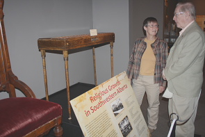 Austin Fennel talks to Wendy Aitkens about one of the pieces in the exhibit. Photo by Richard Amery