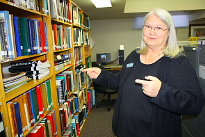 Monta Salmon indicates some of the research material available at the Lethbridge Family History Centre. Photo by Richard Amery