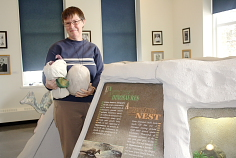 Wendy Aitkens shows off a mock dinosaur egg. Photo by Richard Amery